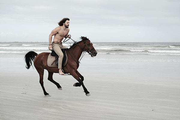 sample image of man riding horse on beach
