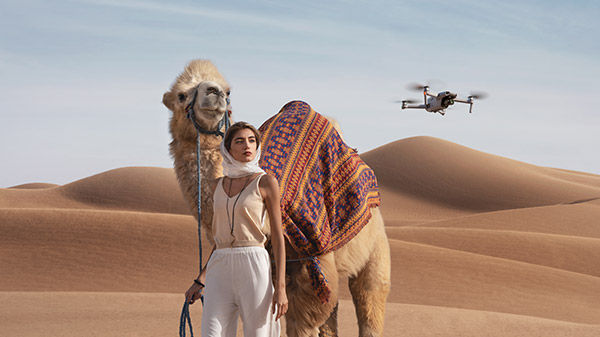 Woman in desert with camel and drone