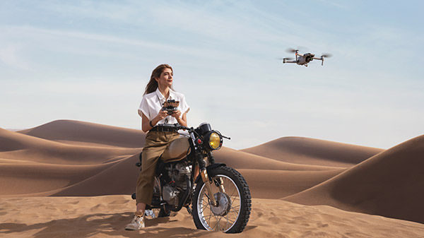 Woman on motorcycle in desert with drone