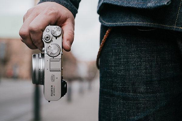 Lifestyle close up image of holding camera