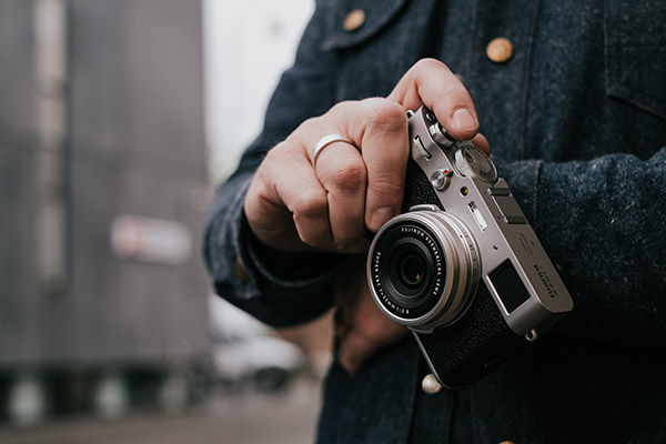 Lifestyle image holding camera while traveling